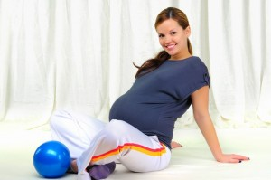 A pregnant woman performing Prenatal Pilates